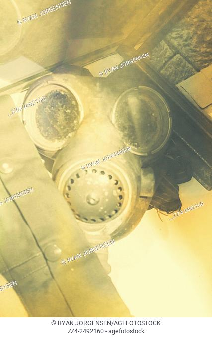 Typical old ww2 photograph of a gasmask in glass case with protective jacket. Reproduction image with slight focal blur, grain and colour fades