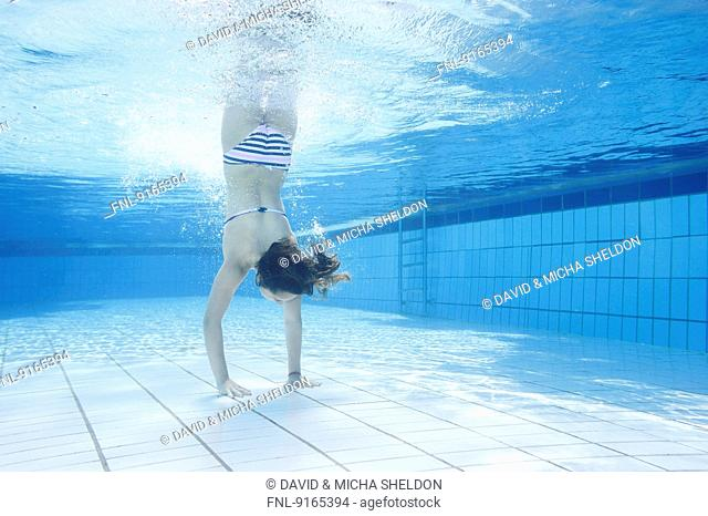 Girl doing a handstand under water in an open-air bath