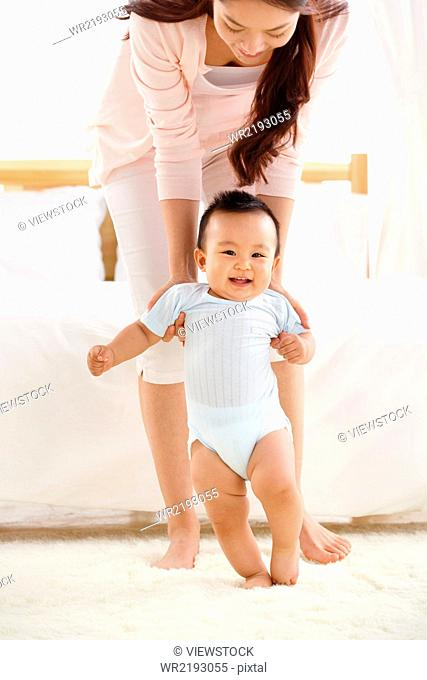 Mother took the baby to learn to walk