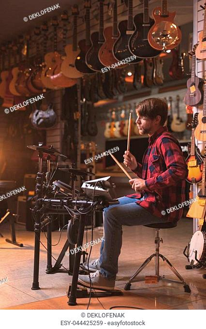 Young musician playing the drums in a music store