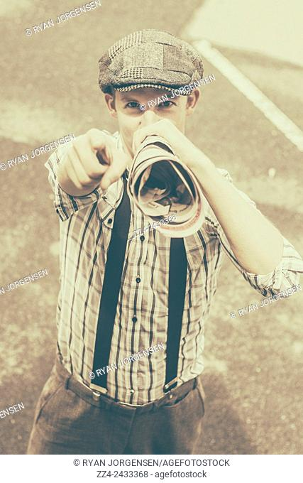 Classic olden day photograph of a vintage newsboy holding news paper megaphone while spruiking editorial information. Printed paper salesman