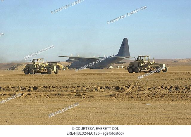 U.S. Navy Seabees run heavy graders down the runway to patch holes and remove excess dirt in the first weeks' occupation of Kandahar on Dec. 18 2001