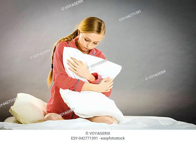 Mental health depression insomia concept. Sad depressive young woman teen blonde girl wearing red pajamas sitting on bed embracing pillow