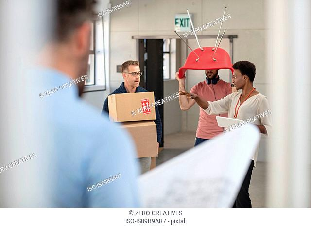 Colleagues in office carrying cardboard boxes and chair