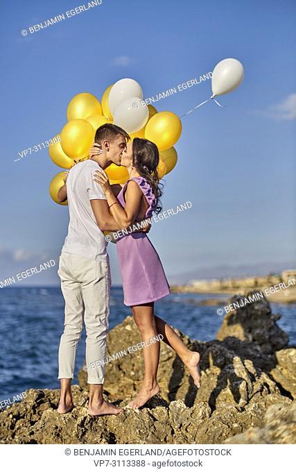 romantic couple kissing, balloons, seaside