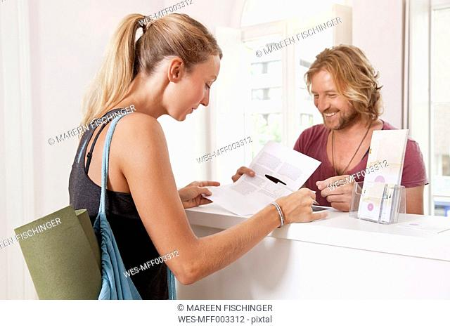 Woman at yoga studio counter filling in contract papers