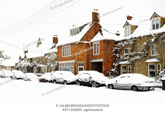 Snow covered village in Oxfordshire with a former post office and row of cottages on the village green