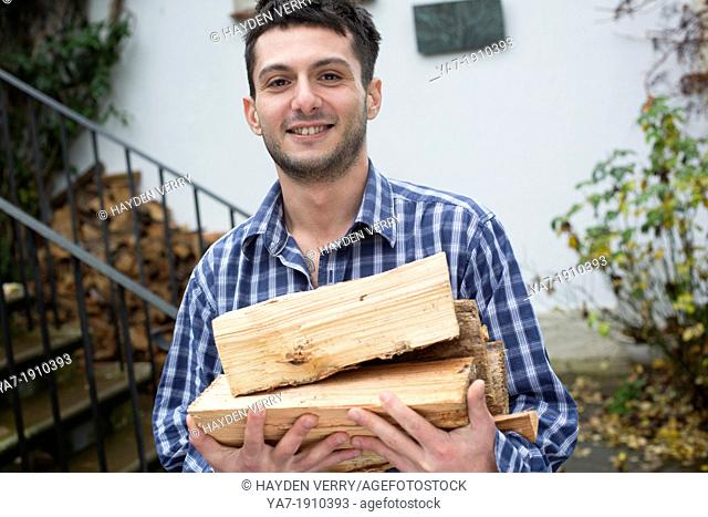 Young Man Carrying Chopped Wood