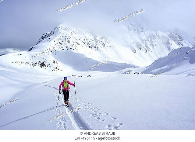 Female ski tourer ascending to Piz Sasuret, Piz Sasuret, Albula Alps, Engadin, Canton of Graubuenden, Switzerland