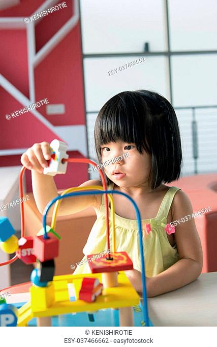 Little Asian girl playing with toy portrait