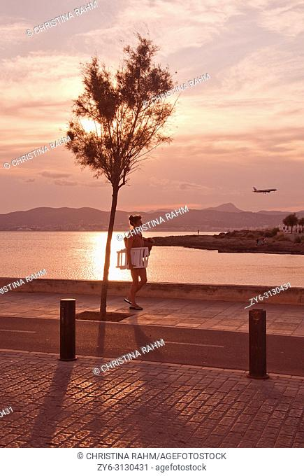 MALLORCA, SPAIN - JULY 21, 2012: Woman walks home from the beach in beautiful landscape at sunset on a sunny summer evening on on July 21, 2012 in Mallorca