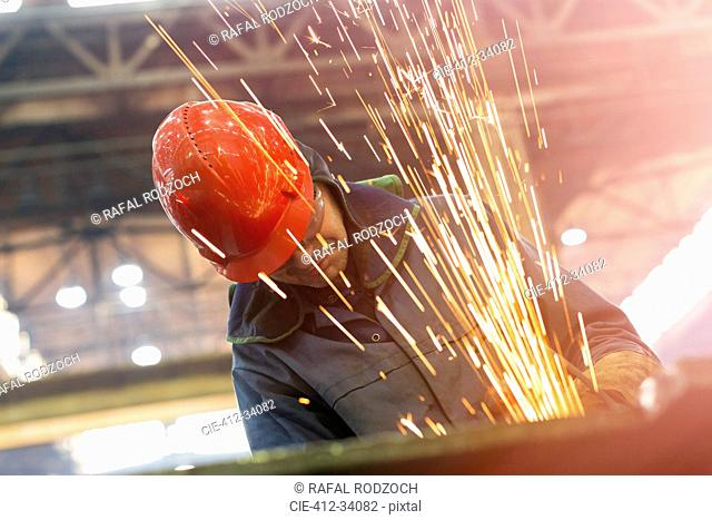 Welder using welding torch with sparks in steel factory
