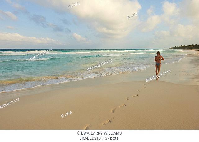 Caucasian girl walking on beach