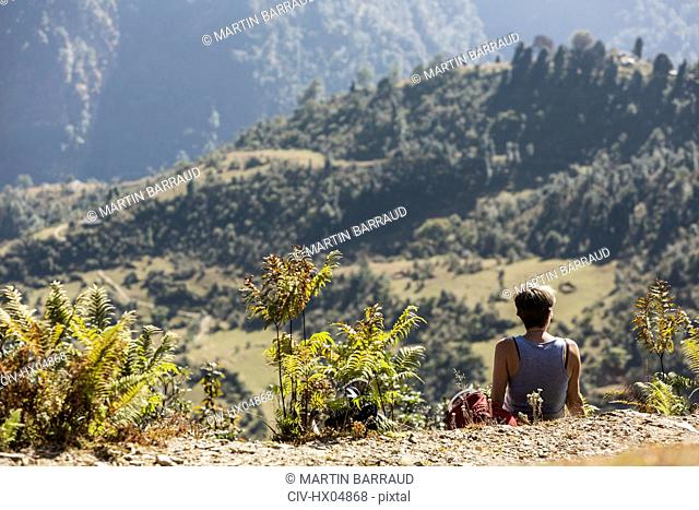 Female hiker resting, enjoying sunny scenic view, Supi Bageshwar, Uttarakhand, Indian Himalayan Foothills