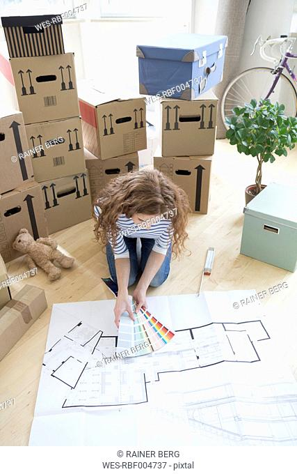 Woman surrounded by cardboard boxes with color samples and construction plan on floor
