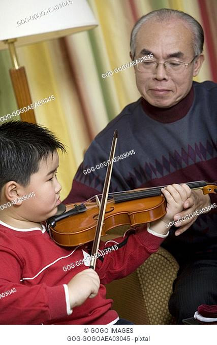 Young boy taking violin lessons