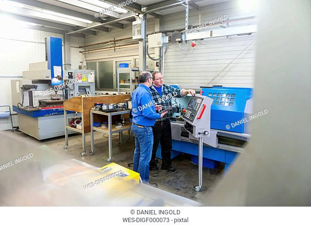 Two men in factory talking at machine for mold making