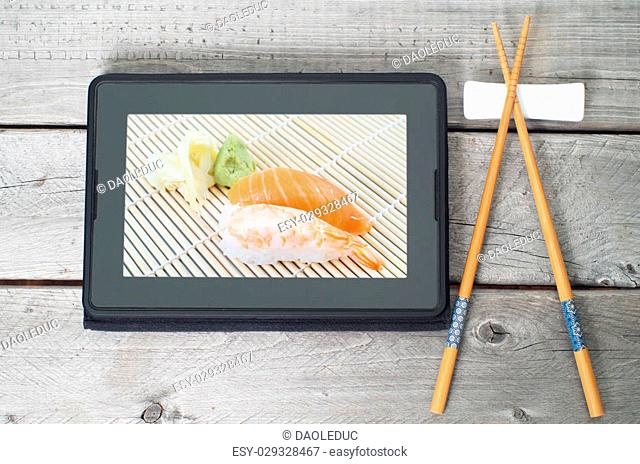 On-line and web asian food ordering concept with digital tablet and chopsticks