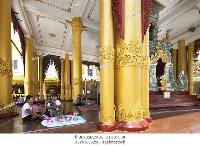 Devotees praying in the Temple with the Sacred hair relic washing well image of the Buddah, Shwedagon pagoda, Yangon, Myanmar, Asia