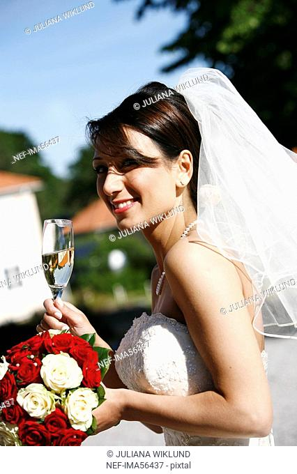 A smiling bride holding a glass of champagne Sweden