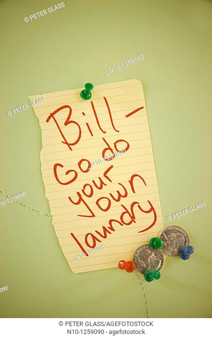 Two American quarters tacked to a bulletin board next to a note reading, 'Bill, go do your own laundry'