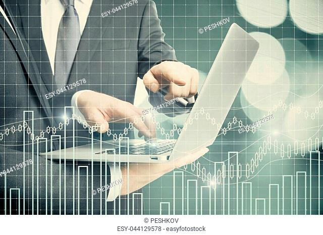 Businessmen using laptop with abstract forex chart on bokeh background. Teamwork and economy concept. Double exposure