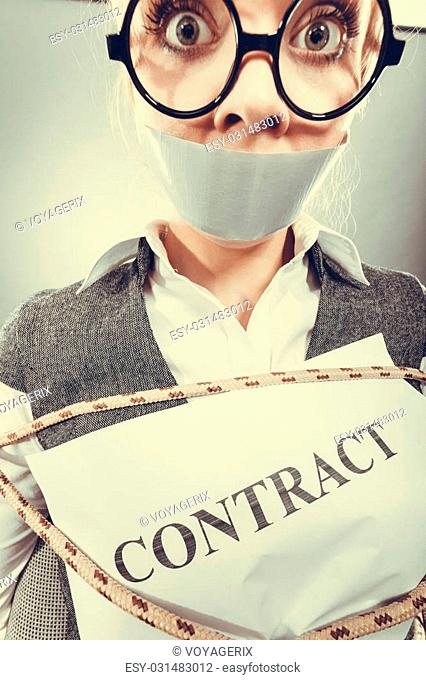 Afraid businesswoman bound by contract terms and conditions with mouth taped shut. Scared woman tied to chair become slave. Business and law concept