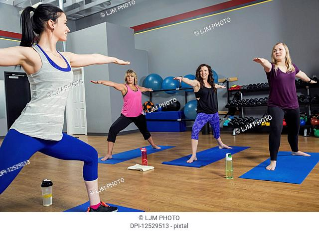 A fitness trainer teaching a warrior pose to her group in a yoga class; Spruce Grove, Alberta, Canada