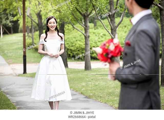 Young romantic wedding couple posing face to face outdoors