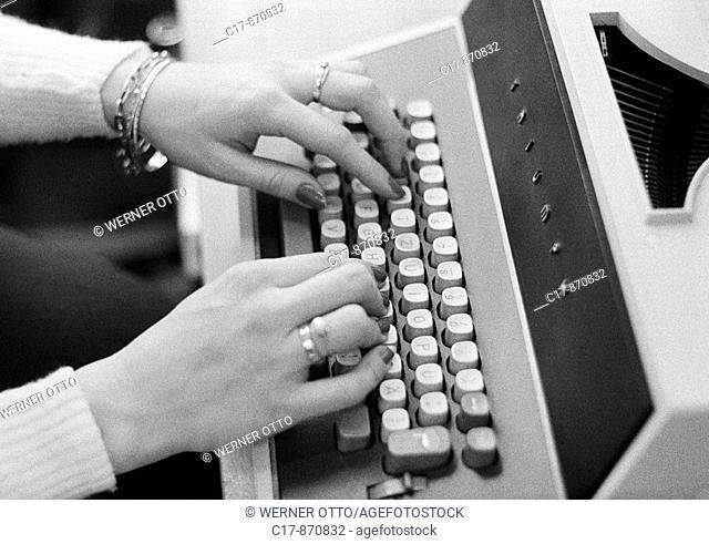 Seventies, black and white photo, economy, work, occupation, office clerk types on a typewriter, hands