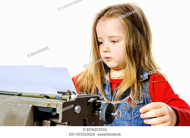 Cute little girl typing letter on vintage typewriter keyboard