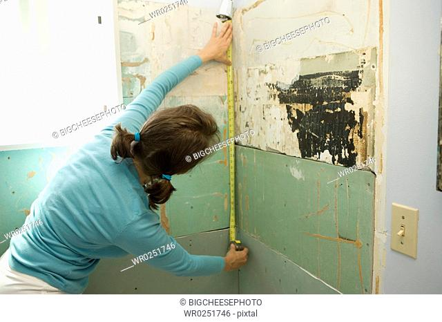 Woman measuring damaged shower wall