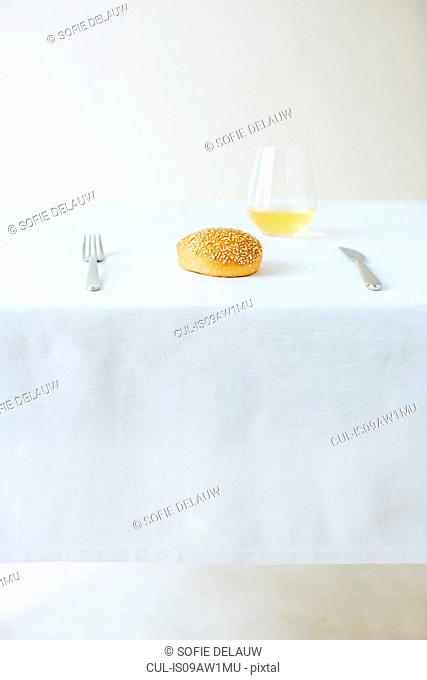 Table setting with simple seeded roll and white wine