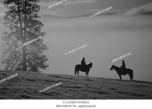 Silhouette of cowboy & cowgirl, Douglas Lake Ranch, British Columbia, Canada'