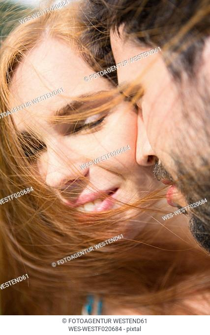 Young couple sharing an intimate moment outdoors