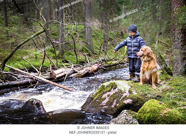 Boy with dog at river