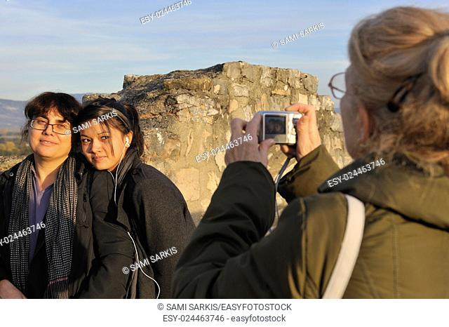 Grandmother taking photo of her granddaughter and daughter outdoors at a tourist destination