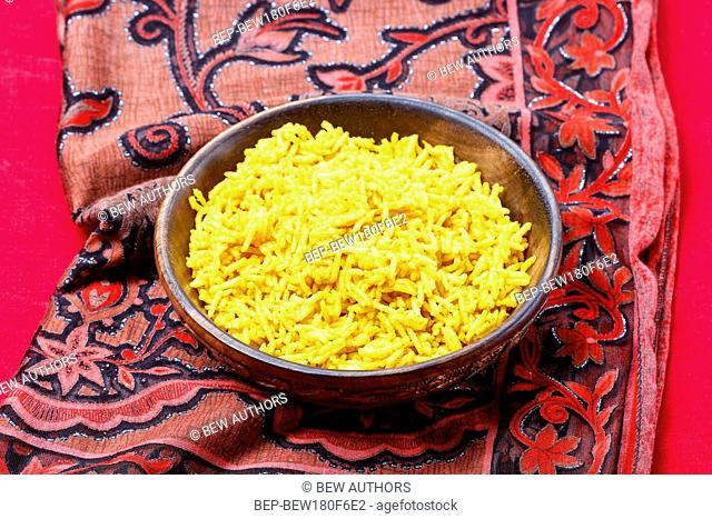 Indian cuisine, bowl of yellow rice on red background