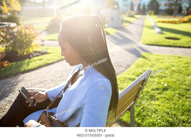 Businesswoman texting with cell phone on sunny park bench