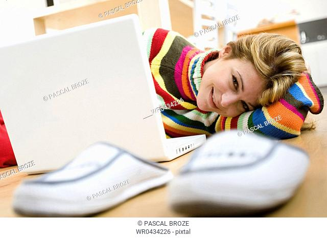 Portrait of a young woman lying in front of a laptop