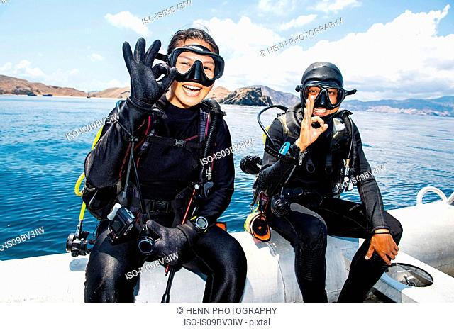 Two scuba divers about to submerge into sea - giving the all ok hand signal, Komodo Island, East Nusa Tenggara, Indonesia
