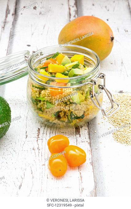 Quinoa salad with avocado, cucumber, tomato and mango in a glass jar