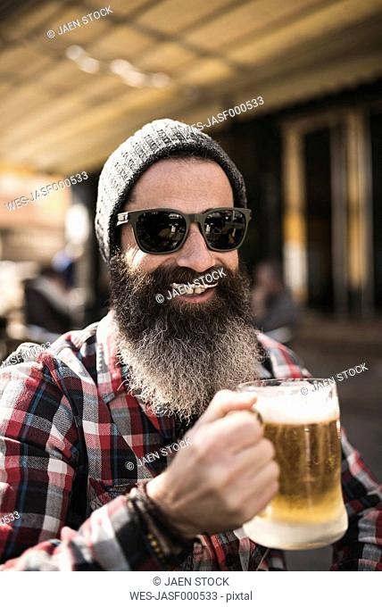 Portrait of smiling hipster with beer foam moustache at outdoor gastronomy