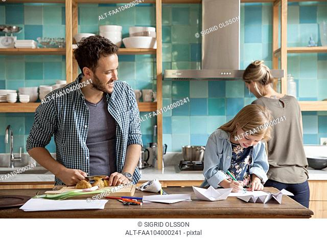 Young daughter drawing ar kitchen counter while parents prepare meal