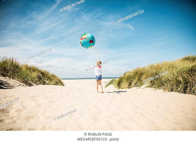 Girl playing with globe on the beach