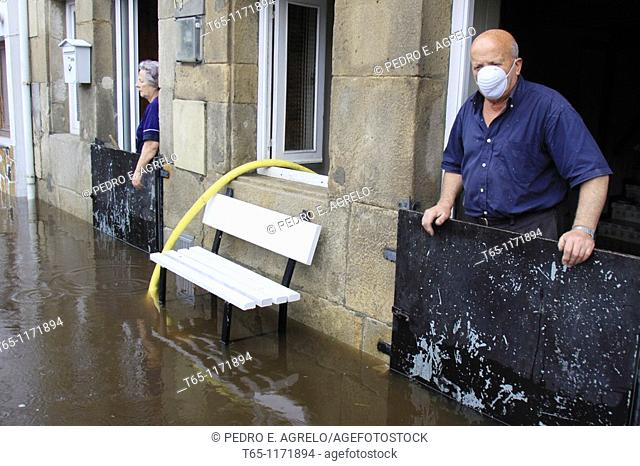 Old couple look at flooded streets after overflowing of River Landro. Viveiro, Province of Lugo, Galicia, Northern Spain