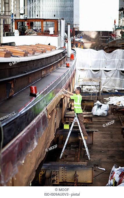Worker on step ladder checking boat in shipyard workshop
