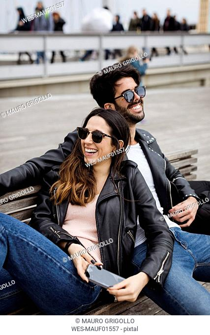 Spain, Barcelona, happy young couple with cell phone resting on a bench