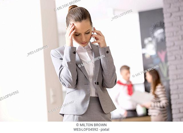 Anxious businesswoman on the phone with couple in background