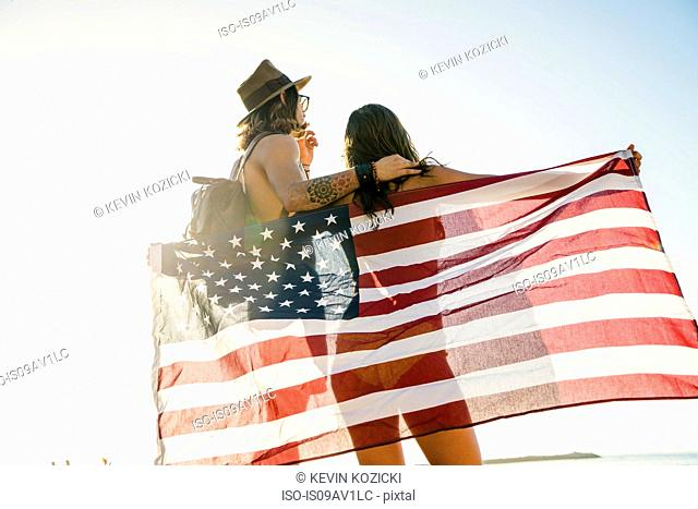 Rear view of young couple wrapped in American flag on Newport Beach, California, USA